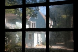 A view from inside of a window, looking out to a nearby house.