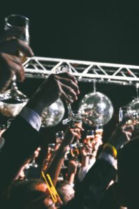people raising their champagne glasses at a party