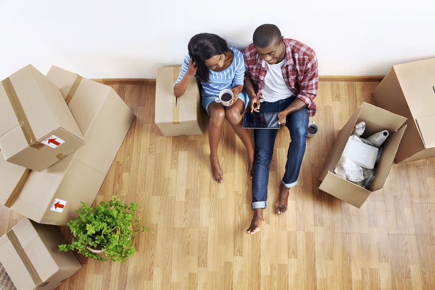 Young couple surrounded by moving boxes in their new home.