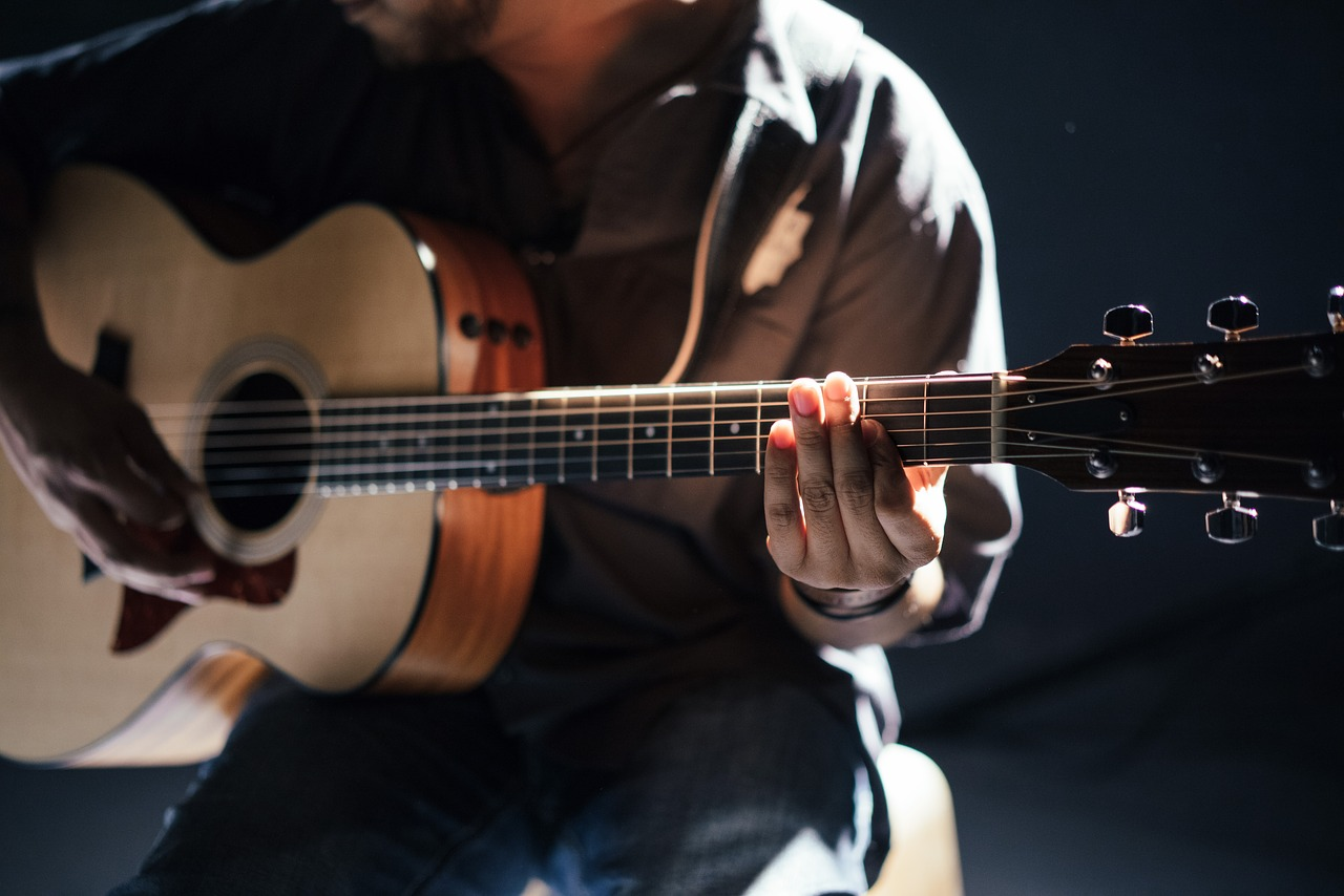 Man holding an acoustic guitar.