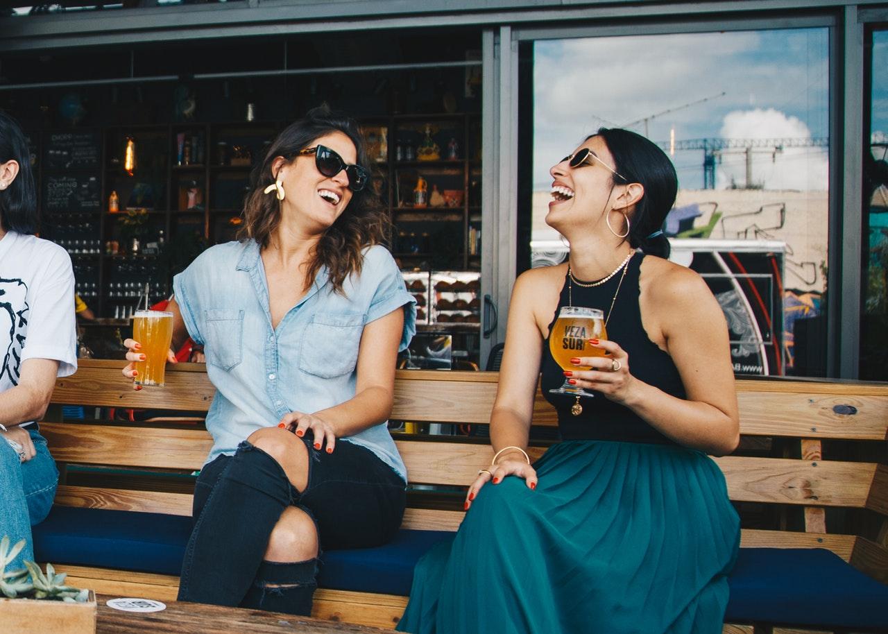 Two women sitting next to each other, holding glasses of beer and laughing.